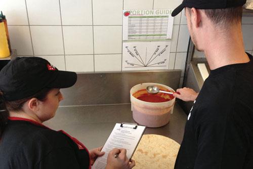 man saucing a pizza